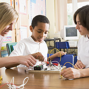 Dozentin mit Jugendlichen beim Elektronikkurs